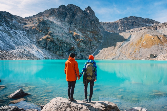Couple of tourists looks at the lake. Honeymoon in Alps. Beautiful turquoise lake in the mountains.